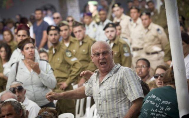 Yoram Tal, dont le fils de 22 ans, Omri, a été tué au combat pendant la guerre de Gaza en 2014, interrompt le Premier ministre Benjamin Netanyahu pendant une cérémonie marquant les deux ans du conflit au cimetière militaire du mont Herzl, à Jérusalem, le 26 juillet 2016. (Crédit : Miriam Alster/Flash90)