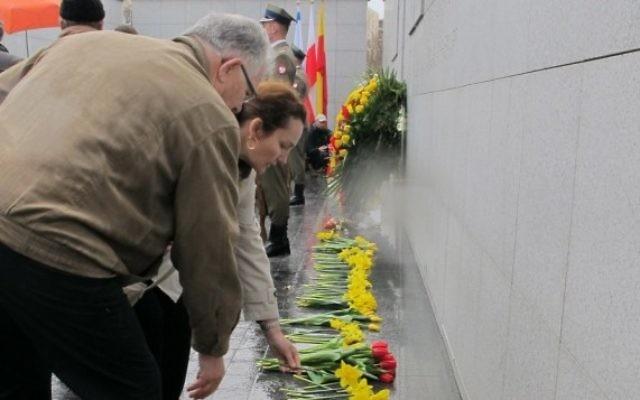 Des gens déposant des fleurs à Umschlagplatz dans le ghetto de Varsovie, là où se trouve le monument en mémoire des Juifs ayant été déportés vers Treblinka. (Crédit : Ruth Ellen Gruber/JTA)