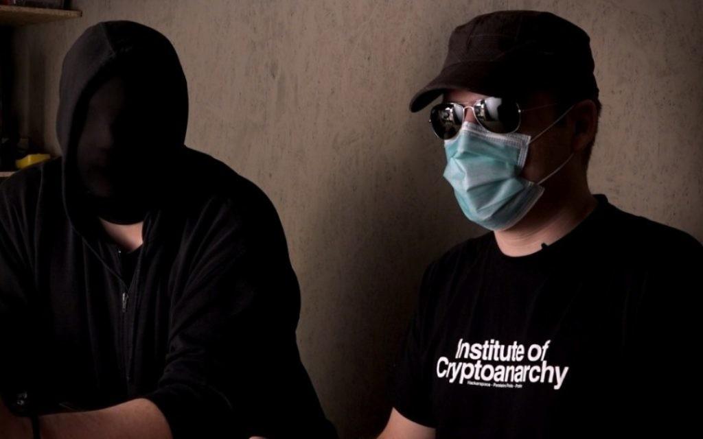 """Des crypto-anarchistes masqués dans une scène de """"Down the Deep, Dark Web. (Crédit : autorisation)"""