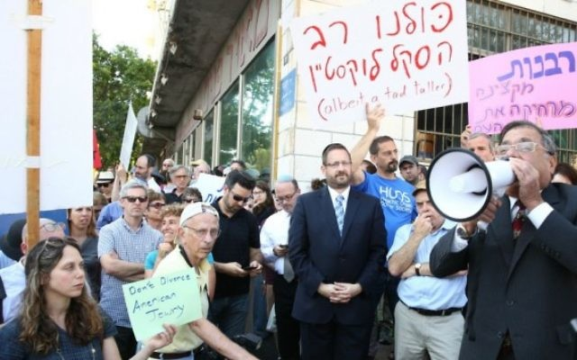 Le grand rabbin d'Efrat Shlomo Riskin parle dans un mégaphone, le 6 juillet 2016, lors d'une manifestation devant les bureaux du grand rabbin de Jérusalem, en soutien aux conversions du rabbin new-yorkais Haskel Lookstein, sous l'œil attentif du chef de l'Agence juive Natan Sharansky et de l'ancien député Dov Lipman (Crédit : Ezra Landau)