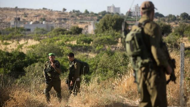 Des soldats de Tsahal gardant la maison où Hallel Yaffa Ariel, 13 ans, a été poignardée à mort par un terroriste palestinien dans l'implantation de Kiryat Arba en Cisjordanie le 30 juin 2016 (Crédit : Yonatan Sindel/Flash90)