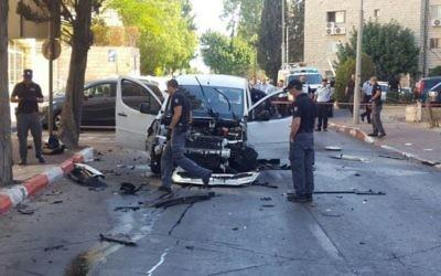 La police inspecte une voiture endommagée par une explosion, rue Mapu, dans le centre de Jérusalem, le 27 juillet 2016. (Crédit : police israélienne)
