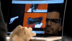 """Yuval Orr parcout l'internet sombre dans une scène de """"Down the Deep, Dark Web. (Crédit : autorisation)"""