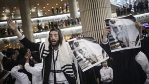 Des Juifs ultra-orthodoxes se rassemblent pour prier lors d'une manifestation de soutien au rabbin Eliezer Berland avant son arrivée à l'aéroport Ben Gourion à Tel Aviv, le 19 juillet 2016. (Crédit photo : Yonatan Sindel/Flash90)
