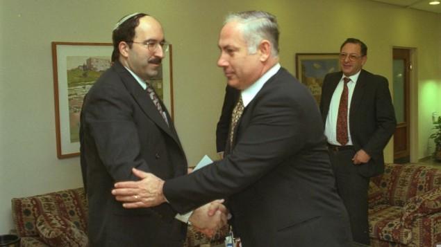 Le Premier ministre Benjamin Netanyahu, à droite, serre la main de Dore Gold, qui était alors son conseiller politique, dans les bureaux du Premier ministre à Jérusalem, en janvier 1997. (Crédit : Avi Ohayon/GPO)