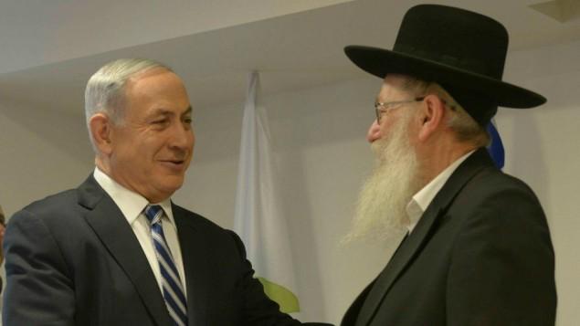 Le Premier ministre Benjamin Netanyahu,  gauche, et le ministre de la Santé Yaakov Litzman, au ministère de la Santé, à Jérusalem, le 20 mai 2015. (Crédit : Amos Ben Gershom/GPO/Flash90)