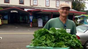 Michael Manor avec un panier de légumes cultivés dans sa ferme biologique. (Photo: Lisa Klug / Times of Israel)