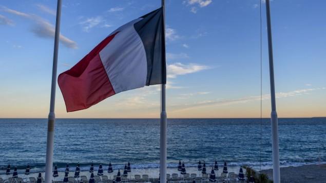 Drapeau français en berne devant une plage vide de la Promenade des Anglais à Nice, au lendemain d'un attentat qui a fait 84 morts, le 15 juillet 2016. (Crédit : David Ramos/Getty Images via JTA)