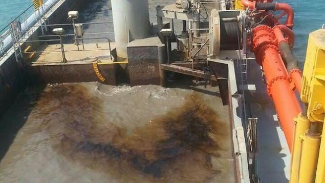 Un navire nettoie une fuite de pétrole dans la baie de Haïfa, le 5 juillet 2016. (Crédit : ministère de l'Ecologie)