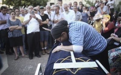 Rina  Ariel pleure sur la dépouille de sa fille de 13 ans, Hallel Yaffa, qui a été poignardée à mort par un terroriste palestinien dans sa chambre, pendant son éloge funèbre, dans l'implantation de Kiryat Arba, le 30 juin 2016. (Crédit : Yonatan Sindel/Flash90)