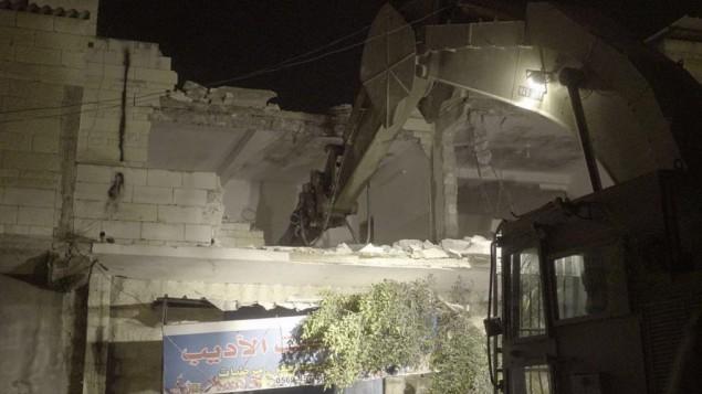 Les forces de sécurité ont détruit le domicile du Palestinien Balal Abu Zeid, qui a été jugé coupable de complicité dans une attaque terroriste pendant laquelle une garde-frontière de 19 ans, Hadar Cohen, a été tuée. La maison d'Abu Zeid à Qabatiya a été démolie le 18 juillet 2016. (Crédit : porte-parole de l'armée israélienne)