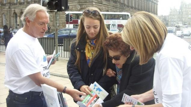 Des volontaires des Amis d'Israël d'Edinbourgh distribuent des informations en faveur d'Israël, dont des prospectus de la Fédération sioniste et des livrets informatifs de StandWithUs (Crédit : autorisation)