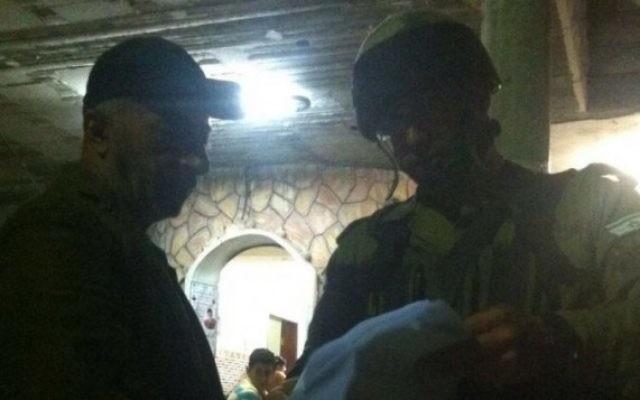 Des soldats israéliens remettent un ordre de démolition à la résidence de Muhammad Tarayrah, le terroriste palestinien de 17 ans qui avait assassiné dans son lit à Kiryat Arba Hallel Yaffa Ariel, 13 ans, à Bani Naim, le 5 juillet 2016. (Crédit : porte-parole de l'armée israélienne)