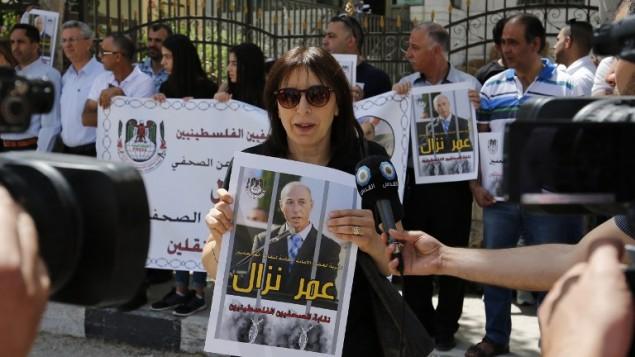 Des journalistes palestiniens manifestent devant les bureaux de la Croix Rouge à Ramallah, en Cisjordanie, pour soutenir leur collègue, Omar Nazzal, placé en détention administrative par Israël, le 24 avril 2016. (Crédit : AFP/Abbas Momani)