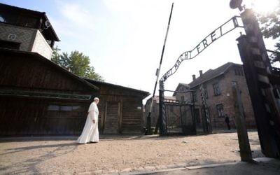 Le pape François passe l'entrée principale de l'ancien camp d'extermination nazi d'Auschwitz-Birkenau, qui porte les mots 'Arbeit macht frei' (le travail libère), à Oswiecim, en Pologne, le 29 juillet 2016. (Crédit : Filippo Monteforte/AFP)
