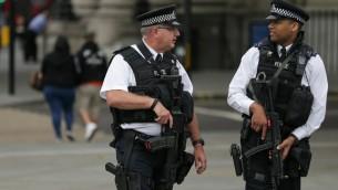 Des policiers armés patrouillent place Trafalgar, à Londres, après une attaque au couteau qui a tué une personne et en a blessé cinq autres, le 4 août 2016. (Crédit : AFP/Daniel Leal-Olivas)