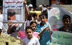 Manifestation de soutien à Mohammed Halabi, directeur pour Gaza de World Vision, à Gaza Ville, le 7 août 2016. (Crédit : Mahmud Hams/AFP)