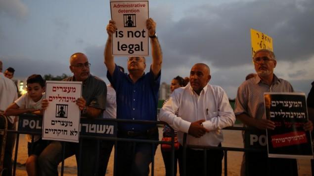 Le député de la Liste arabe unie Ahmed Tibi (au centre) manifeste contre la détention administrative du prisonnier palestinien Bilal Kayed, qui est en grève de la faim depuis 56 jours, devant l'hôpital d'Ashkelon où il est détenu, le 9 août 2016. (Crédit : AFP/Ahmad Gharabli)