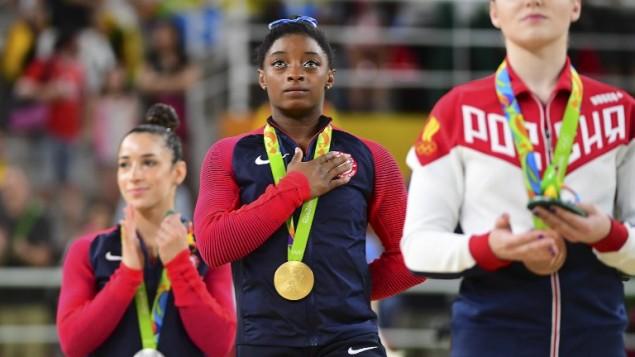 De droite à gauche, la Russe Aliya Mustafina, les gymnastes américaines Simone Biles et Alexandra Raisman sur le podium après le concours général de la gymnastique artistique féminine, aux Jeux olympiques de Rio 2016, le 11 août 2016. Biles a remporté l'événement devant sa compatriote Raisman et Mustafina. (AFP PHOTO / EMMANUEL DUNAND)