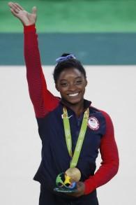 La gymnaste américaine Simone Biles célèbre sa médaille d'or sur le podium après le concours général de gymnastique artistique au cours des Jeux olympiques de Rio 2016, à Rio de Janeiro, le 11 août 2016 (AFP PHOTO / Thomas COEX)