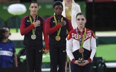 La Russe Aliya Mustafina (à droite), et les Américaines Simone Biles (au centre) et Alexandra Raisman (à gauche), sur le podium de la finale du concours général de gymnastique artistique féminine individuelle au cours des JO de Rio 2016 le 11 août 2016 (AFP Photo/Ben Stansall)