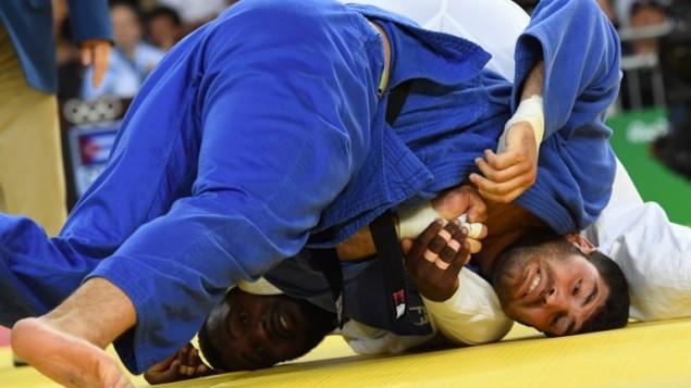 Le Cubain Alex Garcia Mendoza (en blanc) rencontre l'Israélien Or Sasson pendant le tournoi de judo masculin des +100 kg aux Jeux olympiques de Rio, le 12 août 2016. (Crédit : AFP/Toshifumi Kitamura)