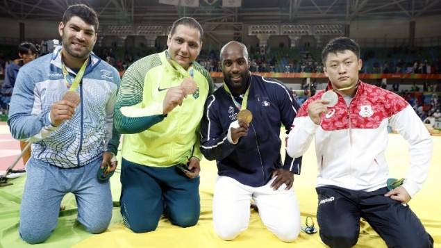 De gauche à droite : l'Israélien Or Sasson (bronze), le Brésilien Rafael Silva (bronze), le Français Teddy Riner (or), le Japonais Hisayoshi Harasawa (argent) célèbrent leurs médailles après la cérémonie du podium du tournoi de judo masculin des +100 kg aux Jeux olympiques de Rio, le 12 août 2016. (Crédit : AFP/Jack Guez)