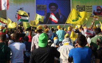 De jeunes hommes agitent des drapeaux libanais ou du groupe terroriste chiite du Hezbollah pendant un discours de Hassan Nasrallah, chef de l'organisation, commémorant les dix ans de la deuxième guerre du Liban, le 13 août 2016. (Crédit : Mahmoud Zayyat/AFP)