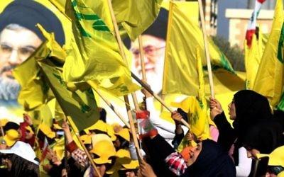 Des femmes agitent des drapeaux libanais ou du groupe terroriste chiite du Hezbollah devant des portraits du guide suprême iranien, l'ayatollah Ali Khamenei (à droite) et le chef du Hezbollah Hassan Nasrallah, pendant un discours de ce dernier commémorant les dix ans de la deuxième guerre du Liban, à Bint Jbeil, le 13 août 2016. (Crédit : AFP/Mahmoud Zayyat)