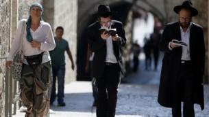 Des Juifs orthodoxes lisent les Lamentations devant l'une des entrées du mont du Temple, le jour de jeûne de Tisha BeAv qui commémore la destruction des Temples de Jérusalem Temples, le 14 août 2016, dans la Vieille Ville de Jérusalem (AFP PHOTO / AHMAD GHARABLI)