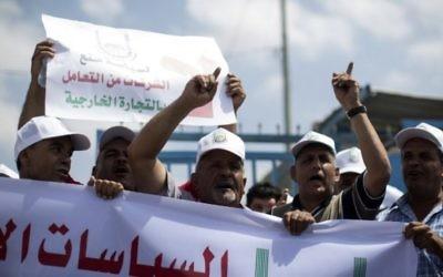 Des hommes d'affaires et des marchands palestiniens manifestant pour protester contre la suspension par Israël de leurs permis de voyage les autorisant à se rendre en Israël et en Cisjordanie, à Beit Hanun, près du poste-frontière d'Erez, dans le nord de la bande de Gaza, le 15 août 2016. (Crédit : AFP/Mahmud Hams)