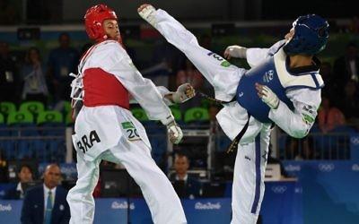 Le combattant israélien Ron Atias (à droite) combattant Venilton Teixeira du Brésil lors de la phase de qualification de taekwondo dans la catégorie homme lors des Jeux Olympiques Rio en 2016, Rio de Janeiro, le 17 août, 2016, (Crédit : AFP / Ed JONES)