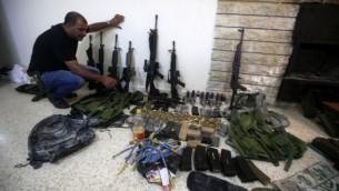 Un membre des forces de l'ordre palestinienne présente des armes que la police a trouvé pendant la recherche de deux hommes armés, toujours en fuite, au poste de police de Naplouse en Cisjordanie, le 21 août 2016. (Crédit : AFP/Jaafar Ashtiyeh)