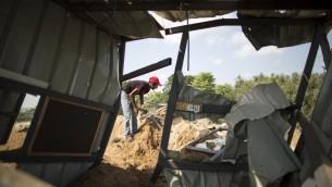 Un homme inspecte les dommages à Beit Lahia, dans le nord de la bande de Gaza, après une frappe aérienne israélienne la veille tirée en réponse à une roquette lancée sur Sdérot, le 22 août 2016. (Crédit : AFP/Mahmud Hams)