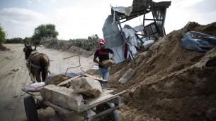Un Palestinien mettant des pierres sur un chariot à côté d'un cratère dans Beit Lahia dans le nord de la bande de Gaza le 22 août 2016, suite à une frappe aérienne israélienne la veille qui a eu lieu la veille (Crédit : Mahmud Hams / AFP)