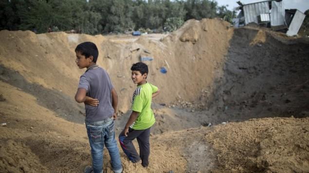 Des enfants palestiniens jouent dans un cratère à Beit Lahia, dans le nord de la bande de Gaza, créé par une frappe aérienne israélienne la veille tirée en réponse à une roquette lancée sur Sdérot, le 22 août 2016. (Crédit : AFP/Mahmud Hams)
