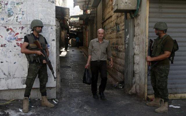 Les membres des forces de sécurité palestiniennes montent la garde alors qu'ils patrouillent la ville de Naplouse en Cisjordanie le 23 août, 2016. (Crédit : AFP/ JAAFAR ASHTIYEH)