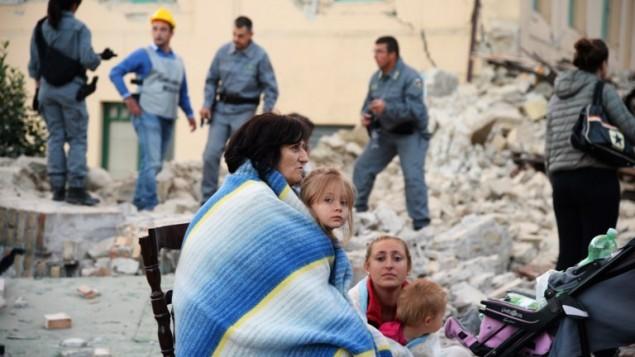 Des victimes assises parmi les décombres des maisons après un fort tremblement de terre à Amatrice, en Italie, le 24 août 2016. (Crédit : AFP/Filippo Monteforte)
