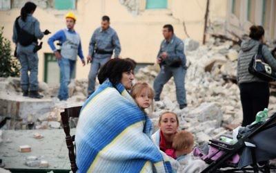 Les victimes assis dans les décombres d'une maison après un fort tremblement de terre qui a frappé Amatrice, Italie, le 24 août 2016 (Crédit : AFP / FILIPPO MONTEFORTE)