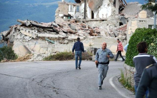 Victimes et sauveteurs parmi les décombres des maisons après un fort tremblement de terre à Amatrice, en Italie, le 24 août 2016. (Crédit : AFP/Filippo Monteforte)