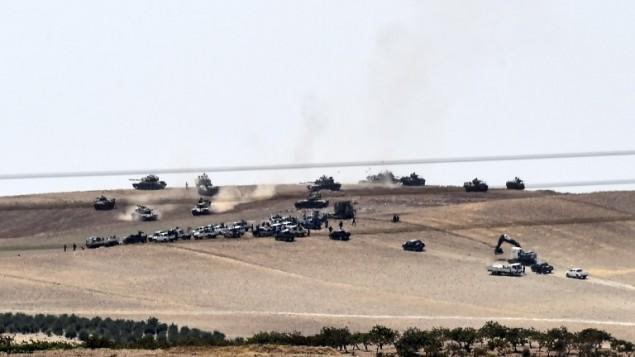 Les tanks turcs et les combattants de l'opposition syrienne pro-Ankara à deux kilomètres à l'ouest de la ville syrienne de Jarablos, à Karkamis, une ville turque frontalière, le 24 août 2016. (Crédit : AFP/Bulent Kilic)