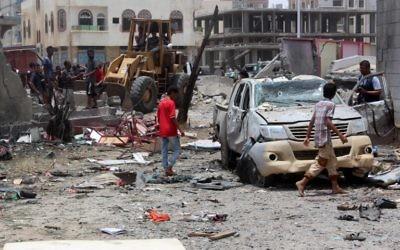 Des Yéménites inspectent le site d'un attentat à la voiture suicide revendiqué par le groupe de l'Etat islamique le 29 août 2016 au centre de recrutement de l'armée dans la ville yéménite d'Aden. (Crédit : AFP/Saleh Al-Obeidi)