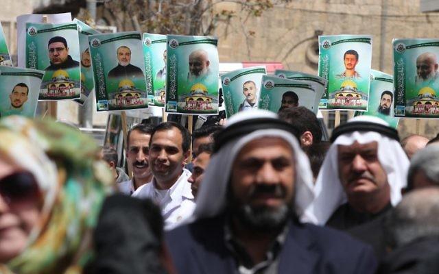 Portraits des membres du groupe terroriste Hamas qui sont emprisonnés dans les prisons israéliennes, lors d'une manifestation de soutien dans la ville de Hébron en Cisjordanie, le 15 avril 2015 (Crédit : AFP PHOTO / HAZEM BADE)