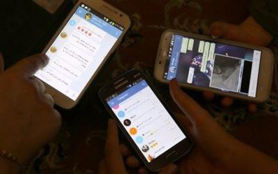 Des Iraniens utilisent l'application Telegram sur leurs téléphones, le 1er décembre 2015. (Crédit : AFP/Atta Kenare)