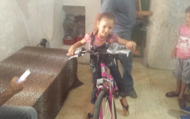 Anwar Burqan, la Palestinienne de 8 ans dont la bicyclette a été détruite par deux gardes-frontière à Hébron, essaie une nouvelle bicyclette achetée pour elle par un Israélien le 17 août 2016. (Crédit : Lonny Baskin)