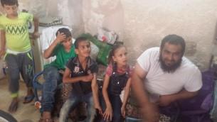 Anwar Burqan, une enfant palestinienne de 8 ans dont la bicyclette avait été détruite par deux gardes-frontières, pose pour une photo avec son père Amer, à droite, et trois de ses frères et sœurs dans leur maison de famille à Hébron, le 17 août 2016. (Crédit : Lonny Baskin)