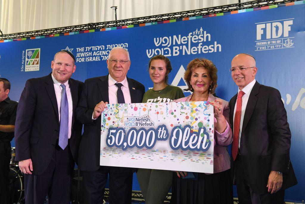 Rebecca Glanzer (eu centre), 22 ans, est la 50 000e personne à faire son alyah via l'association Nefesh B'Nefesh. Elle est entourée, de gauche à droite, du rabbin Yehoshua Fass, fondateur et directeur exécutif de l'organisation, du président Reuven Rivlin, de la ministre de l'Immigration et de l'Intégration Sofa Landver, et de Tony Gelbart, fondateur de Nefesh B'Nefesh, à l'aéroport Ben Gurion, le 17 août 2016. (Crédit : Shahar Azran)