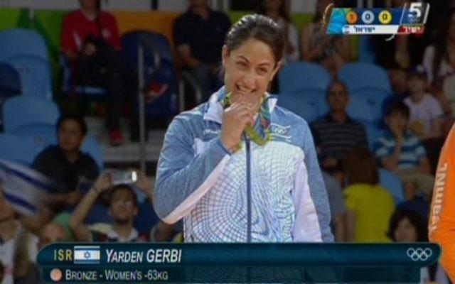 La judokate israélienne Yarden Gerbi mord sa médaille de bronze, obtenue dans le tournoi de judo féminin des -63kg aux Jeux olympiques de Rio, le 9 août 2016. (Crédit : capture d'écran Chaîne 55)