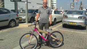 Sami Jolles avec la bicyclette, qu'il a achetée pour Anwar Burqan, dont le vélo avait été détruit par des gardes-frontières à Hébron. (Crédit : Lonny Baskin)