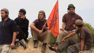Des résidents d'implantation juifs regardent les soldats israéliens affronter des militants palestiniens pendant une manifestation contre les implantations en Cisjordanie, à Hébron. (Crédit : Najeh Hashlamoun/Flash90)